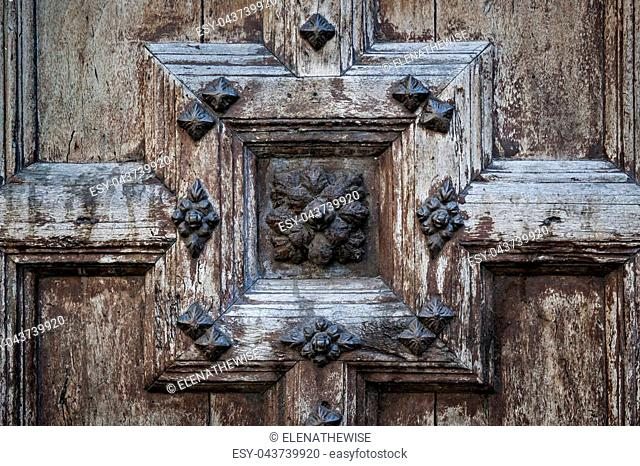 Ornate old wooden door detail of the Church of the Jacobins in Toulouse, France