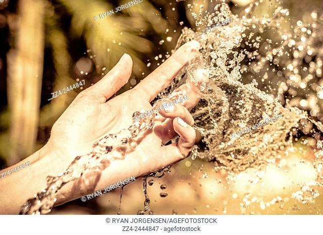 Touch and feel is the motion of water falling through the fingertips of a woman living in the moment. Sensory conceptual