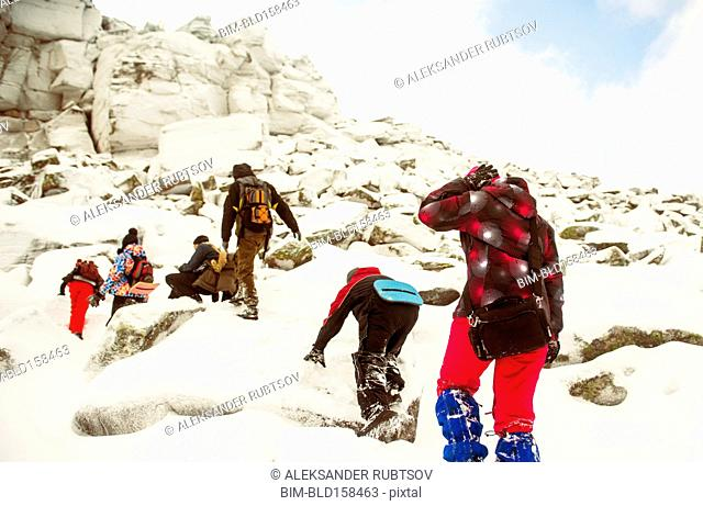 Caucasian hikers climbing snowy rock formations
