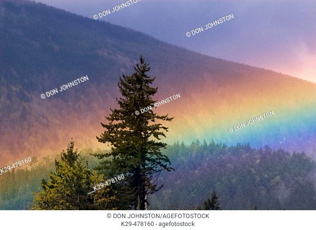Rainbow over mountain slopes, Vancouver Island scenic. Chemainus, BC, Canada