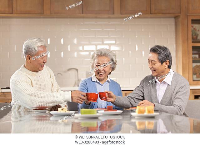 Three friends drinking tea in the kitchen, chinese ethnicity