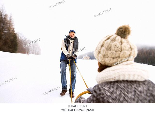 Happy senior couple having fun with sledge in snow-covered landscape