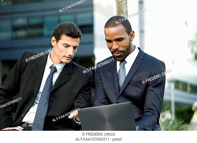 Business colleagues looking at laptop computer together outdoors