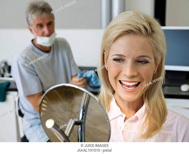 Woman admiring smile in dentist's office