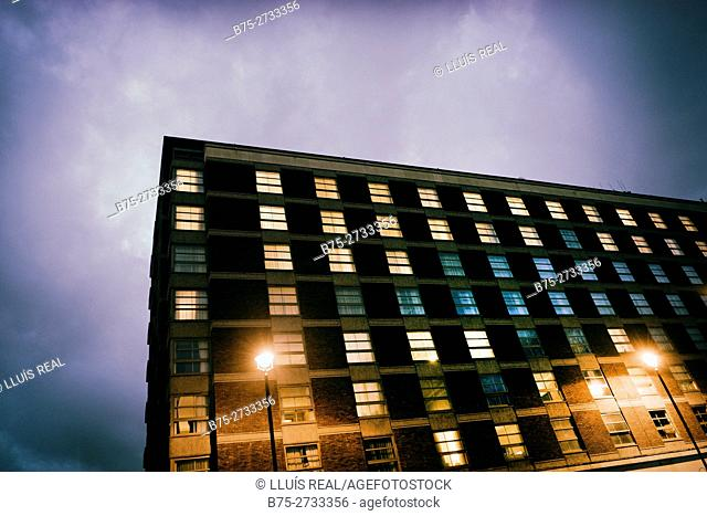Apartment building at night, lights in windows, street lights. London, England