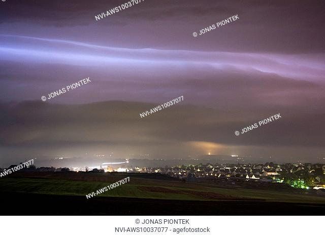 Nighttime shelf cloud of a sheet lightning illuminated, dying thunderstorm behind Langgöns, Hessia, Germany