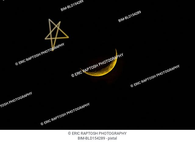 Star drawn by crescent moon in night sky