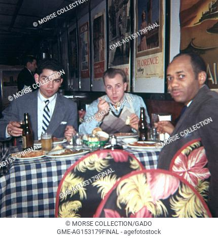 Scene of a Hispanic man, a Caucasian man, and an African American man eating dinner at a crowded table in a restaurant, May, 1962