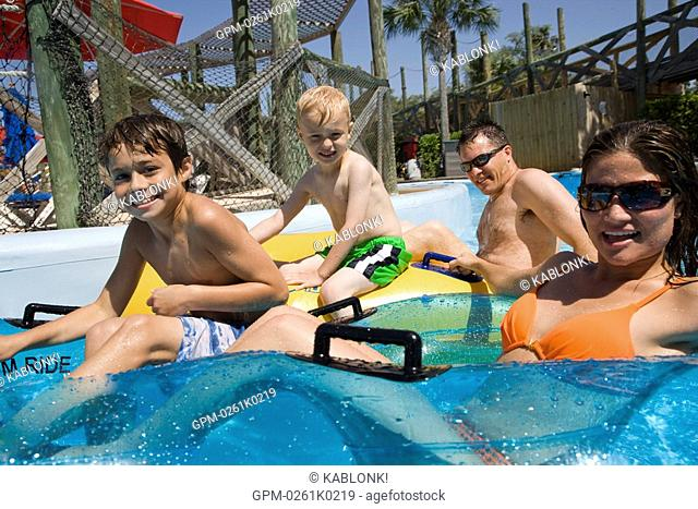 Side view of young family having fun at water park floating on innertubes