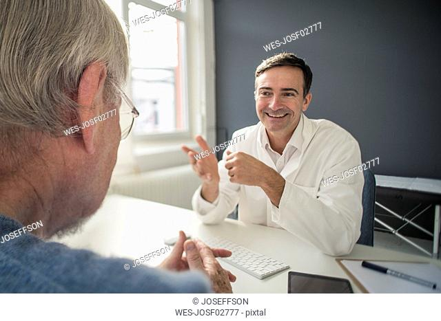 Smiling doctor talking to patient in medical practice