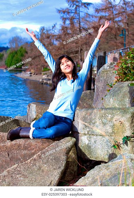 Happy young biracial teen in blue shirt and jeans sitting on large rock by lake shore, arms raised in praise