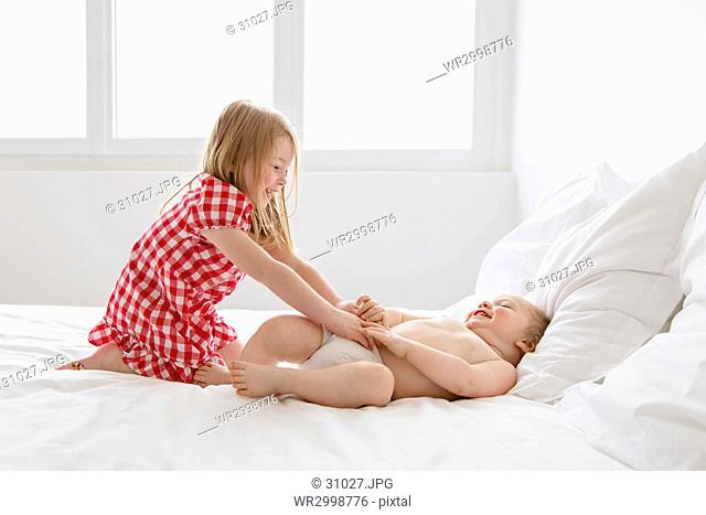 Smiling blond girl wearing red and white checkered dress and baby boy sitting on bed, playing