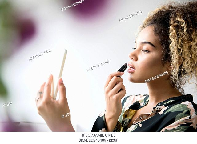 Mixed Race woman holding cell phone applying lipstick