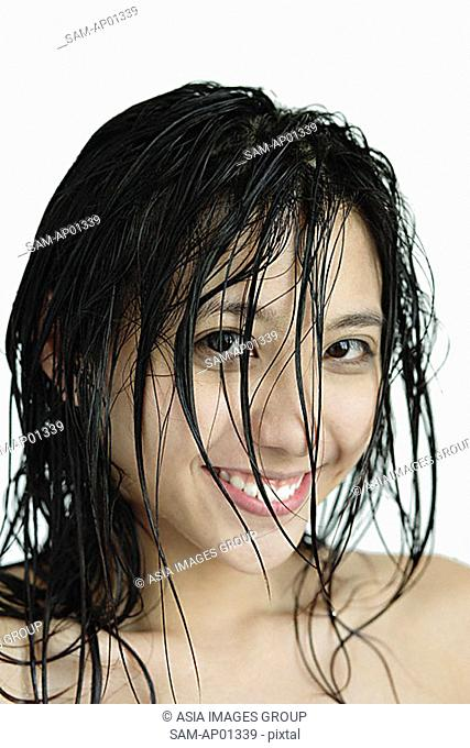 Woman with wet hair, smiling at camera