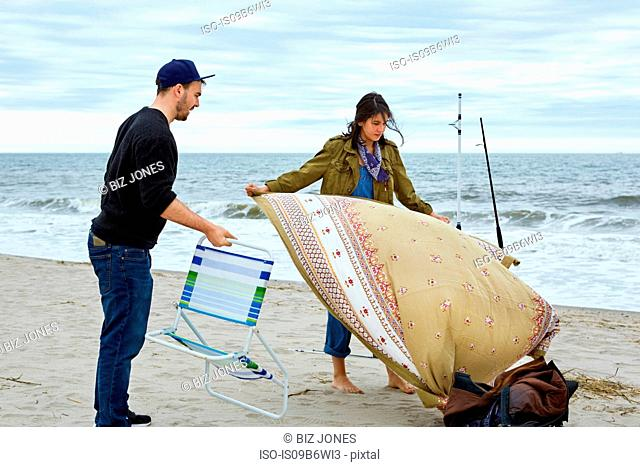 Young sea fishing couple preparing beach chair and picnic blanket on beach