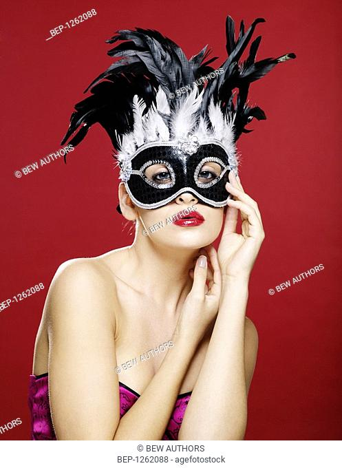 Young woman wearing a carnival mask