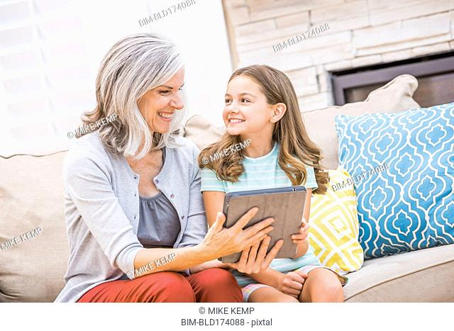 Caucasian grandmother and granddaughter using digital tablet on sofa
