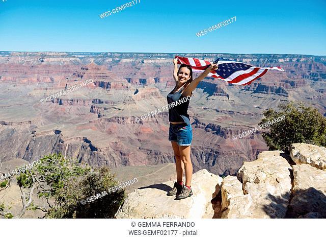 USA, Arizona, smiling woman with American flag at Grand Canyon National Park