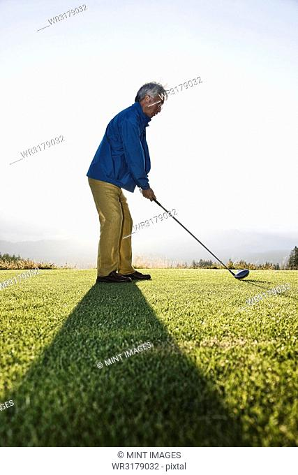 An Asian senior man teeing up a golf ball and ready to swing