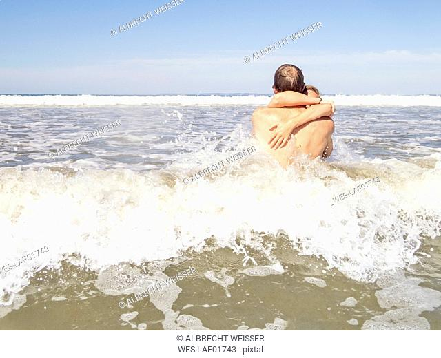 Couple at the beach embracing in the water