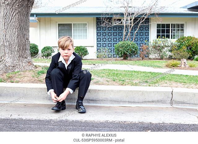 Boy in suit sitting on suburban street