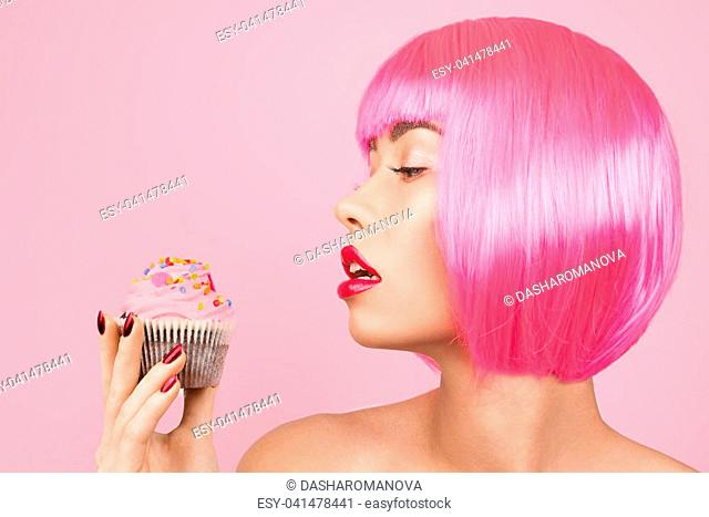 Young pretty woman with makeup eating sweet colourful cupcake