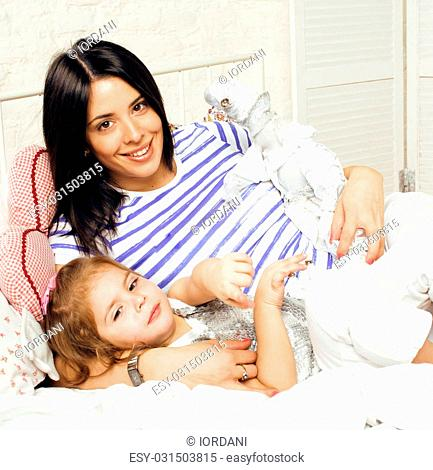 Portrait of smiling young mother and daughter at home, happy family together having fun, lifestyle people concept close up