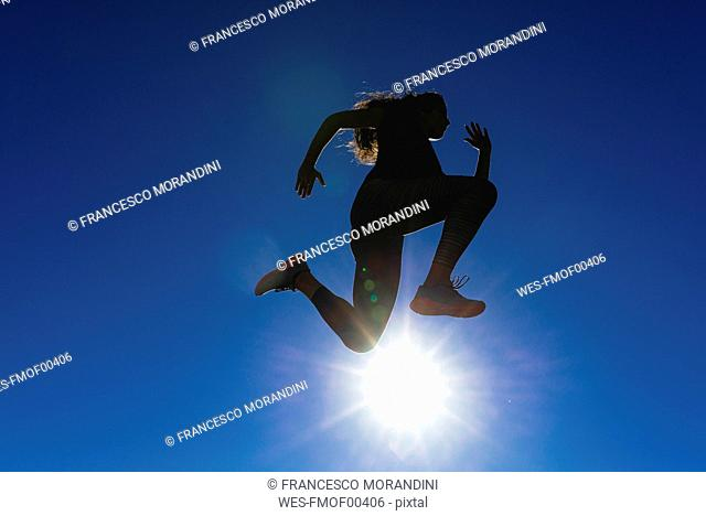 Sportive young woman jumping under blue sky in backlight