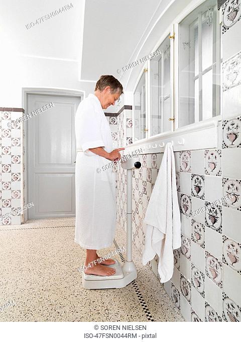 Older woman weighing herself in bathroom