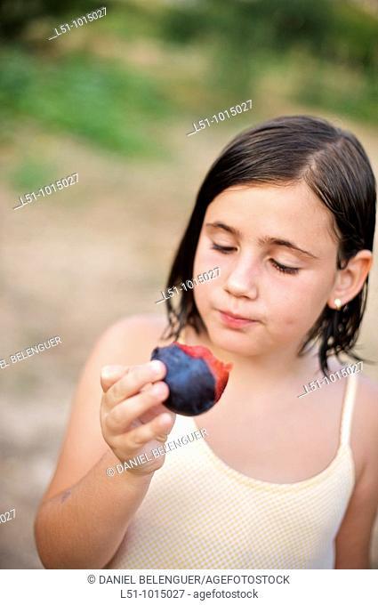 Girl eating a plum