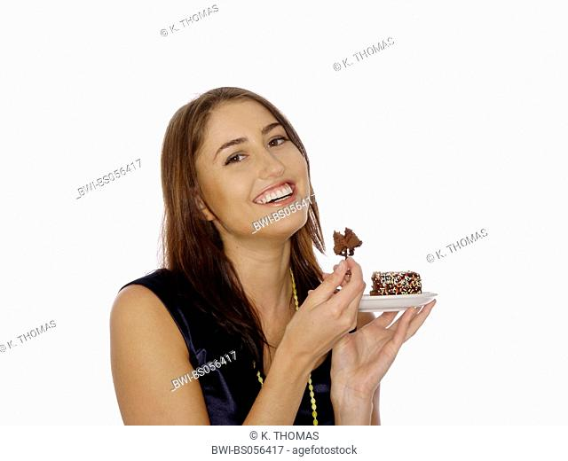 young woman / twen, holding a plate with a peace of cake in her hand, with a bite on a fork, laughing at the camera