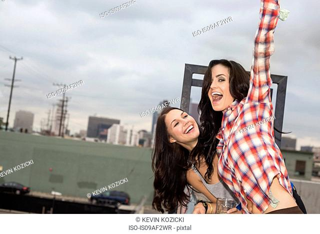 Two female friends jumping around at rooftop party
