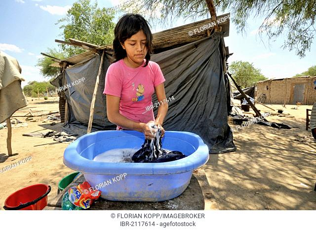 Young woman, 18 years, with indigenous features washing laundry in front of her hut made of plastic tarpaulins, Comunidad Santa Maria, Gran Chaco