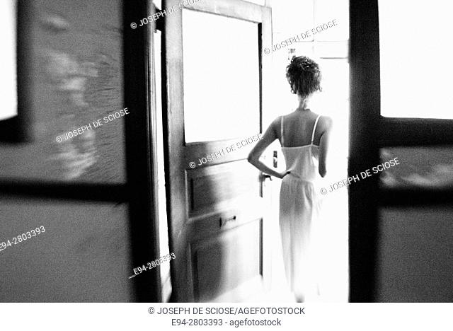 Back view silhouette of a 25 year old woman wearing a white dress walking through a doorway in an abandoned office building