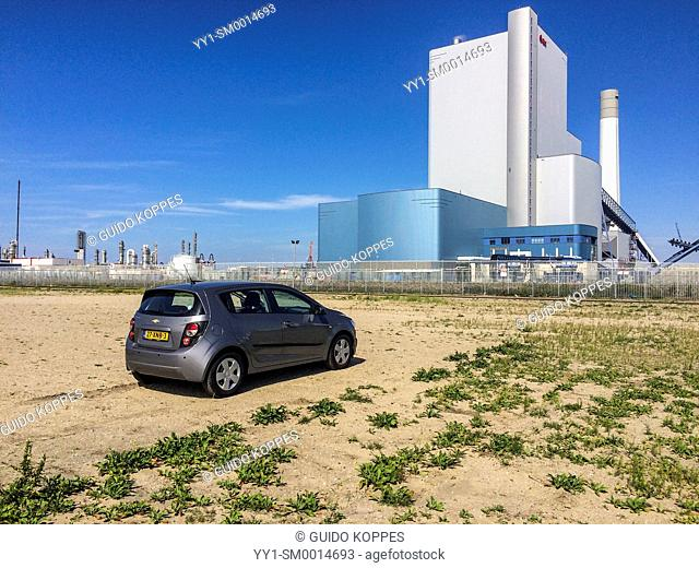 Maasvlakte, Rotterdam, Netherlands. Small car, parked on a field of sands, with a cole fired electricity plant in the background