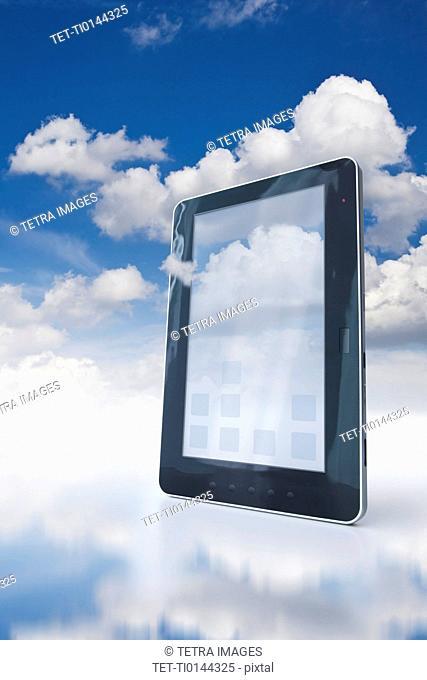 Digital tablet floating in clouds