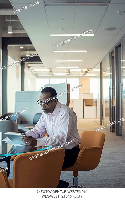 Businessman working alone in office using digital tablet