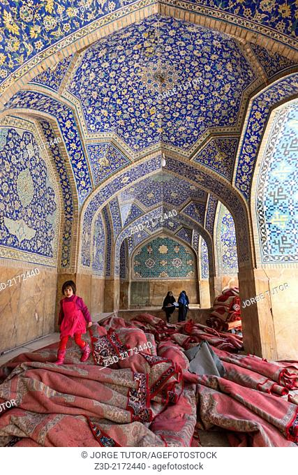 Girl walking over carpet inside Imam Mosque, Isfahan, Iran