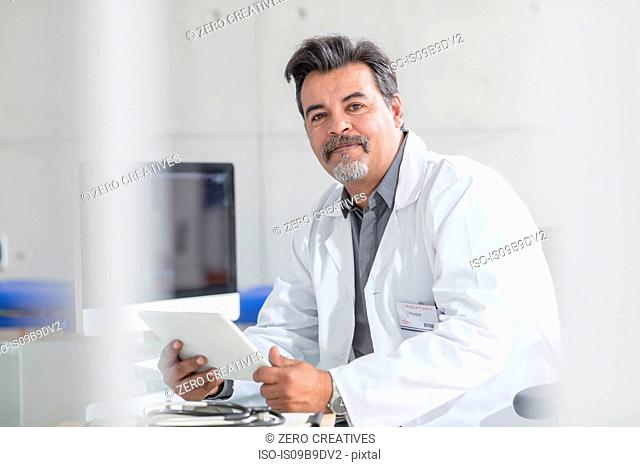 Portrait of male doctor holding digital tablet