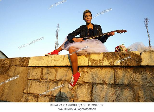 A bride sitting on the platform playing the guitar