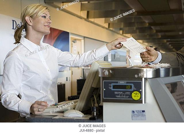Businessman standing at check-in counter, passing ticket to female attendant, smiling, side view