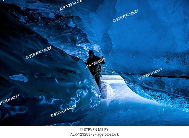 A man inside a Canwell Glacier cave in the Alaska Range in winter