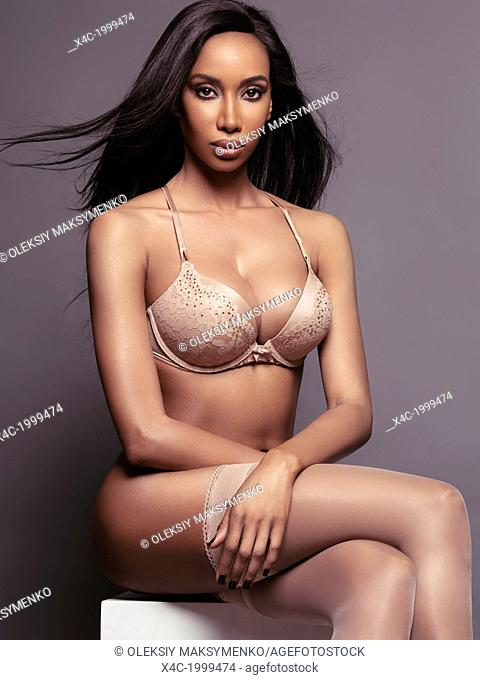 Glamour portrait of a beautiful black woman wearing beige lingerie and stockings isolated on gray studio background