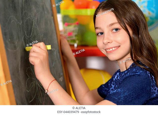 Portrait of cute little girl drawing on chalkboard