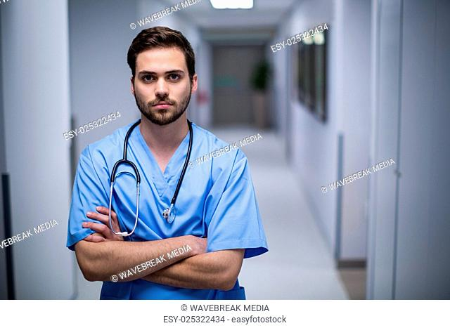 Portrait of male nurse standing in corridor