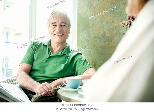 Couple having coffee together, smiling