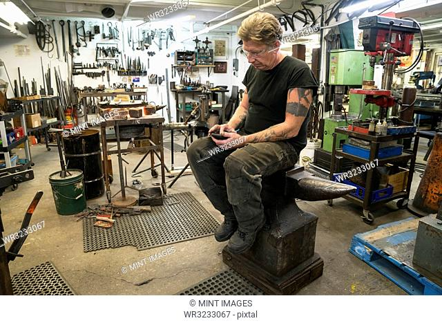 Male Blacksmith checking his phone for messages while sitting on an anvil in his studio