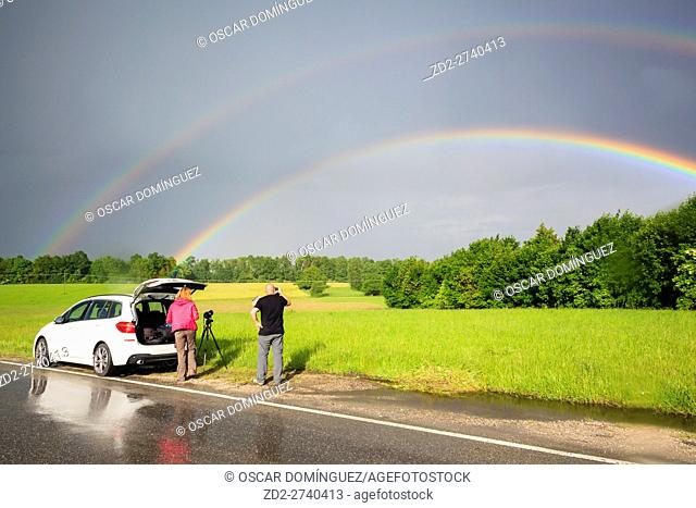 Photographers photographing double rainbow over fields during storm. Upper Bavaria. Germany