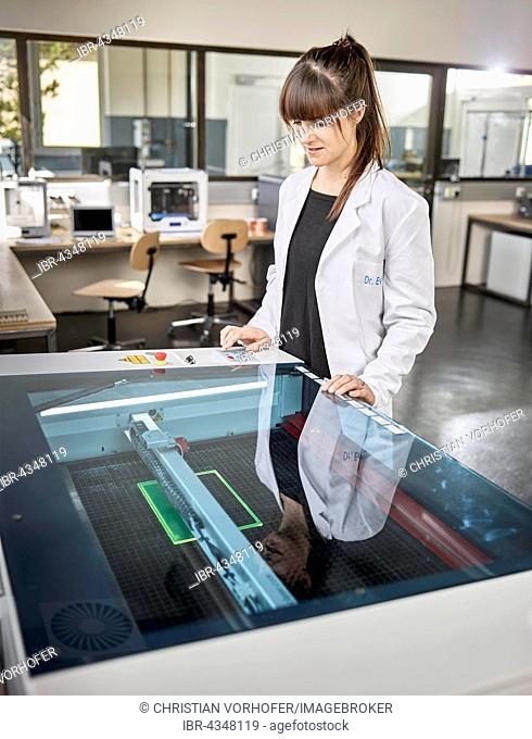 Female technician, 20-25 years, with a white lab coat, using a laser cutter in an electronics laboratory, Wattens, Innsbruck Land, Tyrol, Austria