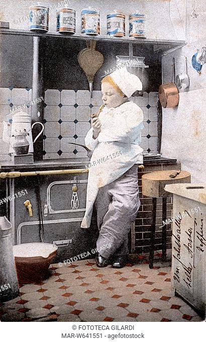 CUCINA in scala ridotta a misura di bambino che recita la parte del cuoco. Il bimbo si da un contegno fumando la pipa a braccia conserte
